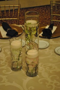 A trio of submerged orchids with curly willow swirled in the vases and a floating candle to accent each vase.