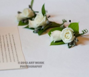 The men's boutonnieres included white garden tea roses and silver grey pods to accent.